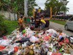 petugas-kebersihan-berusaha-mengangkut-tumpukan-sampah.jpg