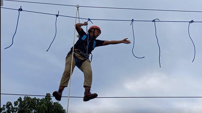 Wisatawan berjalan di atas tali salah satu wahana permainan yang ada di Lokasi Bendungan Raknamo, Kabupaten Kupang, Provinsi NTT