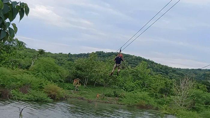 Wisatawan terbang diatas air bendungan raknamo, salah satu wahana permainan yang ada di Lokasi Bendungan Raknamo, Kabupaten Kupang, Provinsi NTT