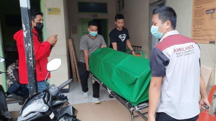 Petugas menggotong jenazah MA untuk dikebumikan di kampung halamannya.