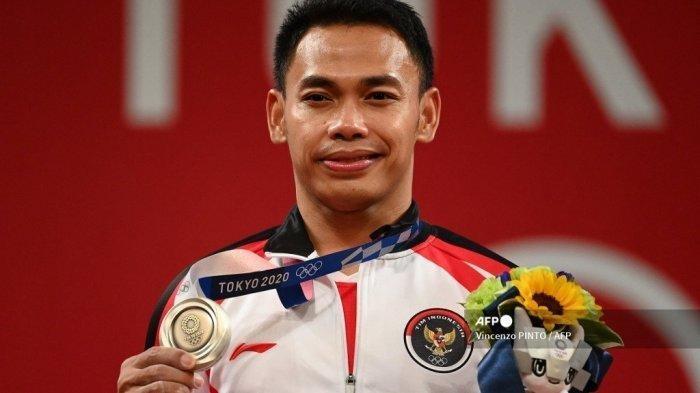 Peraih medali perak Indonesia Eko Yuli Irawan berdiri di podium untuk upacara kemenangan kompetisi angkat besi 61kg putra selama Olimpiade Tokyo 2020 di Tokyo International Forum di Tokyo pada 25 Juli 2021.