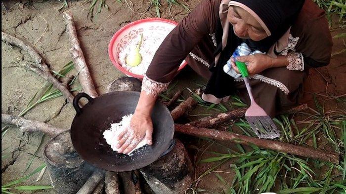 Perempuan paruh baya memasak gedah sagu menggunakan tangan di wajan panas di kawasan destinasi wisata Lae Trup, Rawa Singkil, Desa Teluk Rumbia, Kecamatan Singkil, Aceh Singkil, Selasa (7/7/2020).