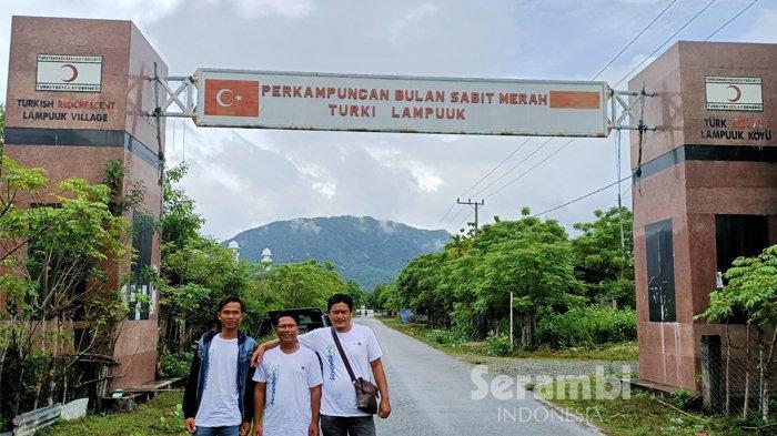 Pengunjung berfoto di depan gerbang masuk perkampungan Lampuuk, Aceh Besar, November 2020. Kampung Lampuuk yang hancur dihantam tsunami 26 Desember 2004, dibangun kembali oleh Pemerintah Turki dan lembaga kemanusiaan negara itu.