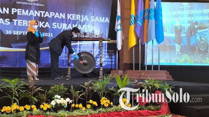 Direktur Universitas Terbuka Surakarta, Yulia Budiwati dan Wakil Rektor Bidang Pengembangan Institusi dan Kerjasama Universitas Terbuka, Rahmat Budiman memukul gong sebagai simbol pemukaan kerjsama di Hotel Novotel Solo, Kamis (30/9/2021).