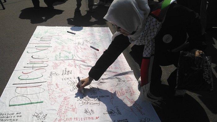 Direktur Yayasan Diwa Center, Diah Warih Anjari, menandatangani spanduk sebagai aksi solidaritas peduli Palestina, Minggu (2/12/2018) pagi.
