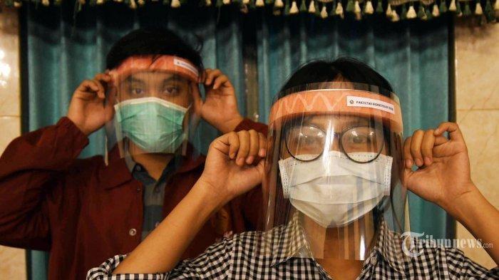 FACE SHIELD SEDERHANA - Dua mahasiswa mencoba face shield sederhana buatan mahasiswa Fakultas Kedokteran Universitas Airlangga di sela tugas kuliah onlinenya di aula FK Unair, Senin (23/3/2020).