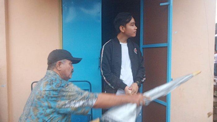 Berjaket PDI Perjuangan, Gibran Terabas Hujan Blusukan di Kampung Joho Manahan