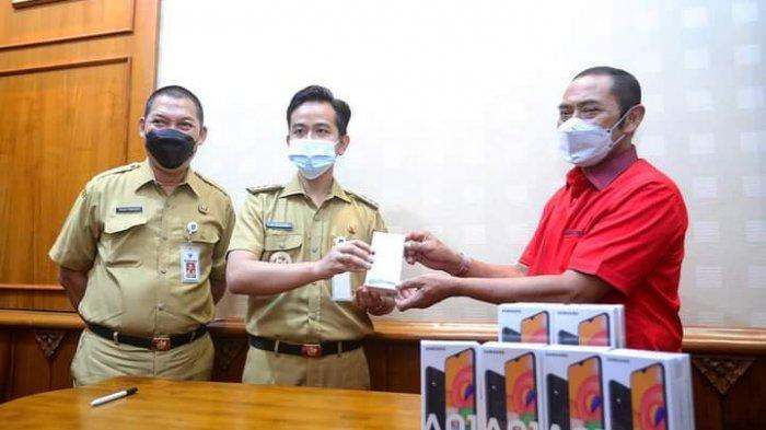 Ketua DPC PDI Perjuangan Kota Solo, FX Hadi Rudyatmo memberikan bantuan HP bagi siswa tak mampu ke Wali Kota Solo, Gibran Rakabuming Raka di Balai Kota Solo, Senin (8/3/2021).