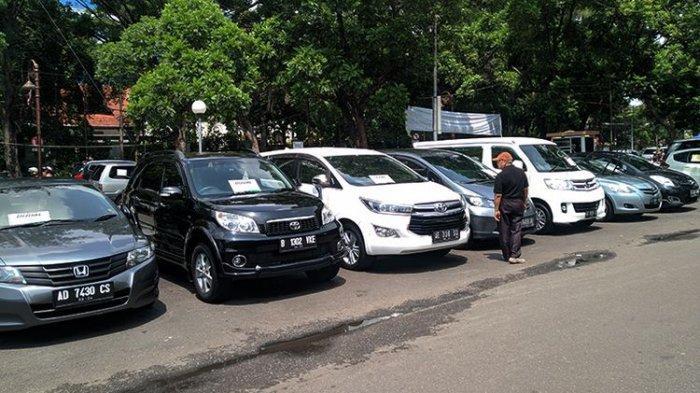 Seorang pengunjung melihat deretan mobil bekas yang dipajang di bursa mobil Sriwedari, Solo, Jawa Tengah (Jateng), Minggu (15/12/2019).