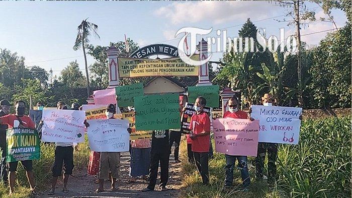Warga membawa poster karena keberatan harga ganti rugi Tol Solo-Jogja di Desa Joton, Kecamatan Jogonalan, Kabupaten Klaten, Selasa (24/8/2021).