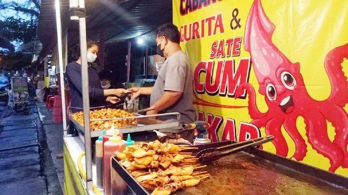 Penjual sate cumi-cumi bakar ala Street Food in Bangkok melayani pembeli di Jalan Menteri Supeno, kawasan Stadion Manahan, Kacamatan Banjarsari, Kota Solo, Jumat (9/4/2021).
