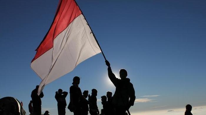 Pendaki mengibarkan bendera Indonesia di atas puncak Gunung Prau di saat hari kemerdekaan Indonesia.