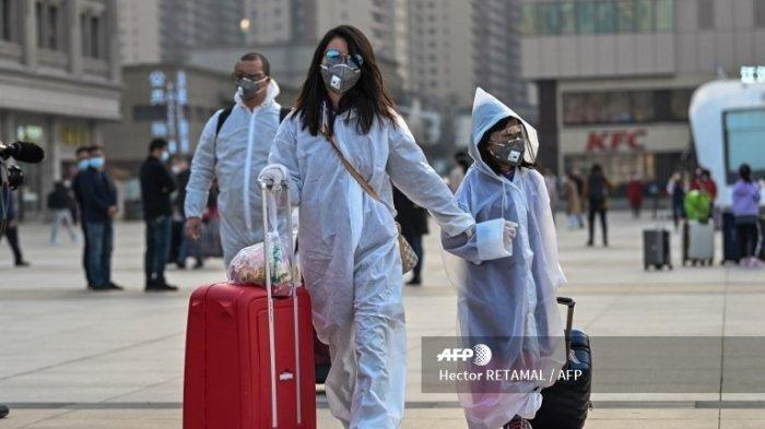 Orang-orang yang mengenakan pakaian pelindung dan masker tiba di Stasiun Kereta Api Hankou di Wuhan, untuk naik salah satu kereta api pertama yang meninggalkan kota di provinsi Hubei tengah China awal 8 April 2020. Pihak berwenang Cina mencabut larangan lebih dari dua bulan pada perjalanan keluar dari kota di mana pandemi global pertama kali muncul.