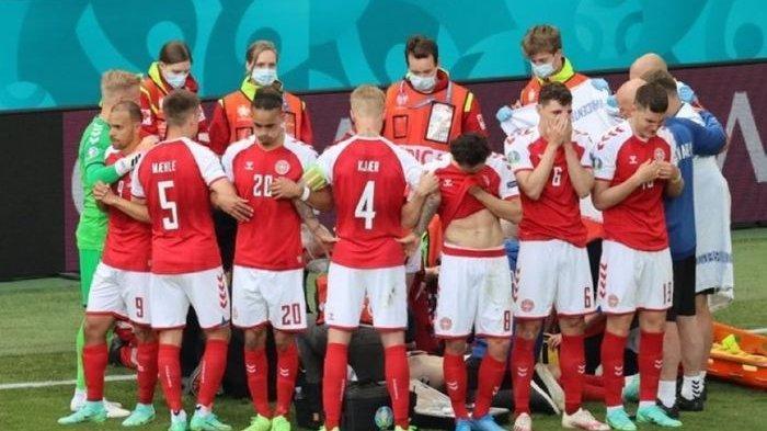 Para pemain timnas Denmark mengelilingi Christian Eriksen yang sedang menerima perawatan.