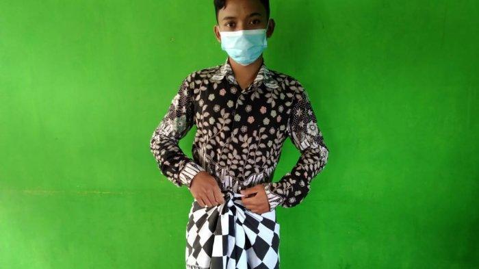 Seorang relawan Pemuda Hindu Cetho memberikan contoh yang benar dalam mengenakan kain kampuh pada Minggu (10/1/2021)