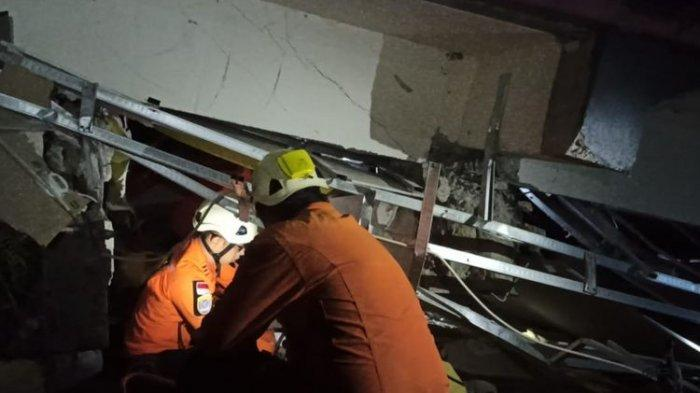 Petugas Basarnas sedang mengevakuasi korban yang terjebak reruntuhan sebagai dampak gempa di Mamuju, Sulawesi Barat, Jumat (15/1/2021)