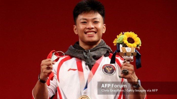 Atlet angkat besi Indonesia, Rahmat Erwin Abdullah berposes dengan memegang medali perunggu dalam angkat besi nomor 73 kg di Tokyo International Forum, 28 Juli 2021 (Chris Graythen/Getty Images/AFP).