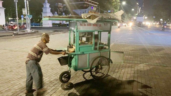 Sukimin (88) alias Mbah Min saat pelan-pelan mendorong gerobak baksonya khas Wonogiri di kawasan simpang lima Gladag, Jalan Mayor Sunaryo, Kecamatan Pasarkliwon, Kota Solo, Senin (19/4/2021).