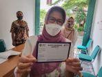epala-dinas-kesehatan-kota-dkk-solo-siti-wahyuningsih-menunjukkan-kartu-vaksin.jpg
