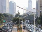 kendaraan-padat-merayap-dengan-latar-belakang-gedung-bertingkat-yang-diselimuti-asap-polusi.jpg