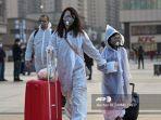 orang-orang-yang-mengenakan-pakaian-pelindung-dan-masker-tiba-di-stasiun-kereta-api-hankou.jpg
