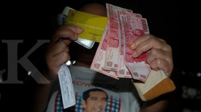 ILUSTRASI. Penerima Program Simpanan Keluarga Sejahtera (PSKS) Rohma, menunjukkan persyaratan Kartu Perlindungan Sosial (KPS) dan dana Bantuan Langsung Tunai (BLT) yang diterimanya di Kantor Pos Indonesia, Bandung, Jabar, Selasa (18/11).