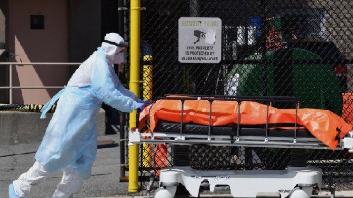 Seorang petugas medis sedang membawa jenazah pasien corona di sebuah rumah sakit di Brooklyn, New York, Amerika Serikat, untuk dipindahkan ke truk pendingin.