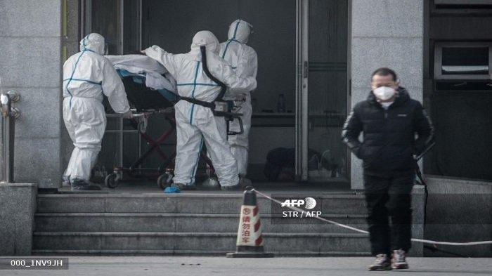 Anggota staf medis membawa seorang pasien ke rumah sakit Jinyintan, di mana pasien yang terinfeksi oleh virus mirip SARS (virus corona) sedang dirawat, di Wuhan, Hubei, China (18/1/2020). (STR-AFP)