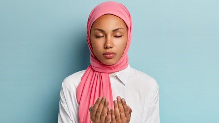 Ilustrasi wanita berhijab berdoa.