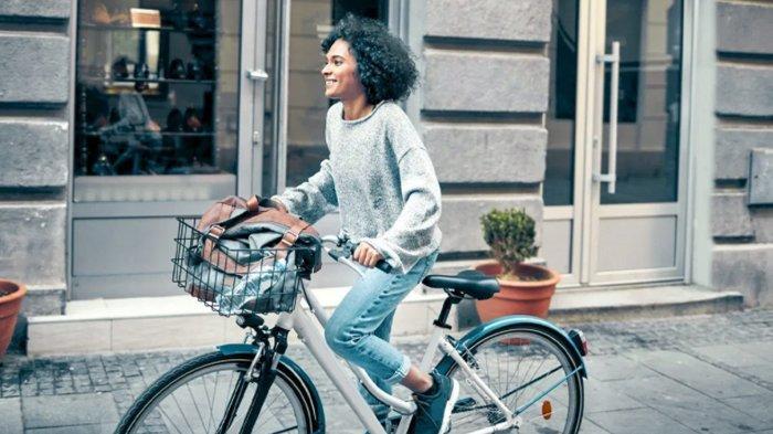 Ilustrasi wanita naik sepeda.