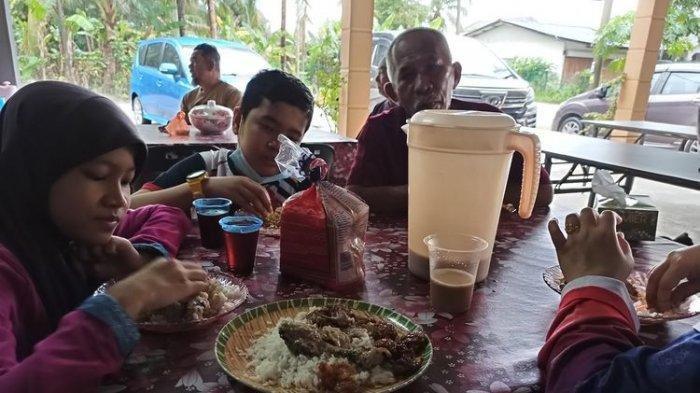 Keluarga Azam Mahat menikmati hidangan di salah satu rumah yang disangkanya warung di Kelantan, Malaysia, pada 2 Januari.