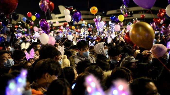 Orang-orang yang memakai masker wajah memadati jalan untuk menghitung mundur Tahun Baru di Wuhan di provinsi Hubei tengah China pada 31 Desember 2020.