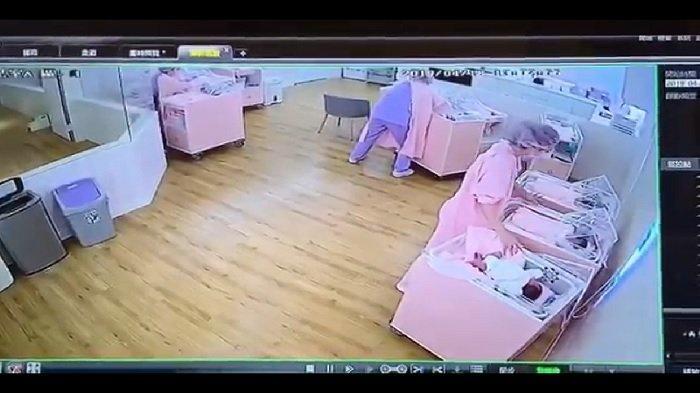 Perawat yang mencoba menenangkan bayi saat gempa terjadi.