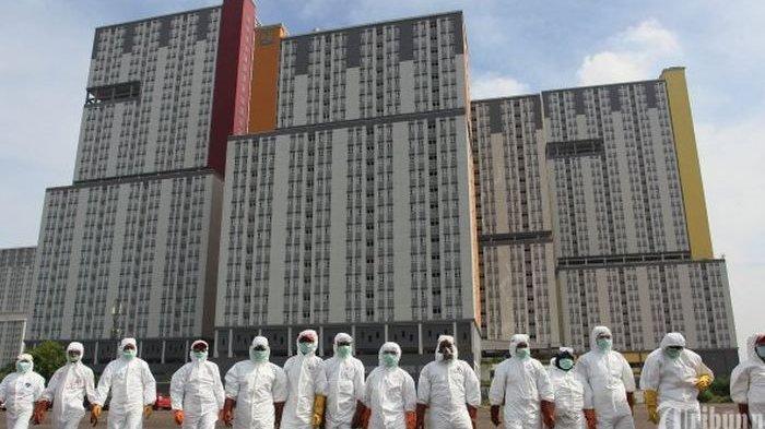 Petugas PMI bersiap melakukan penyemprotan cairan disinfektan untuk membersihkan Wisma Atlet Kemayoran