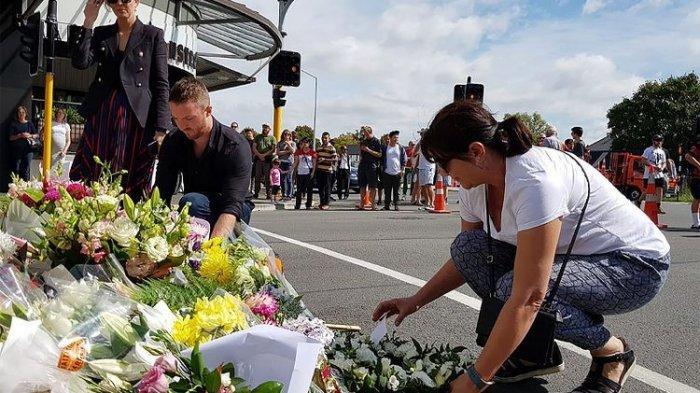 Warga kota Christchurch, Selandia Baru meletakkan karangan bunga untuk mengungkapkan rasa duka terkait penembakan masjid yang menewaskan 49 orang pada Jumat (15/3/2019).(AFP/GLENDA KWEK)
