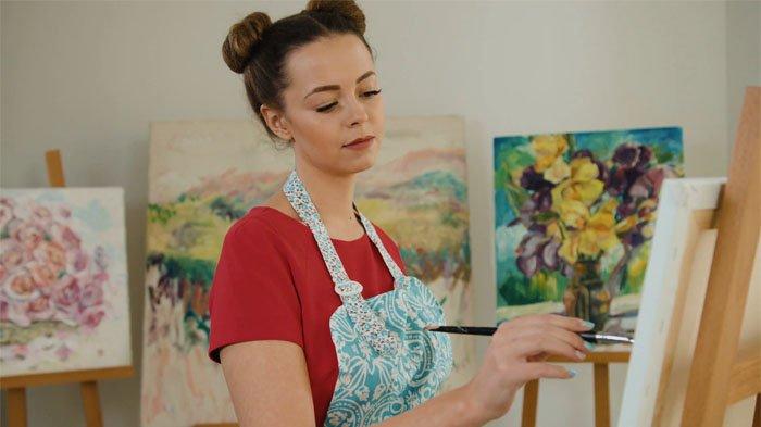 Seorang wanita melukis.