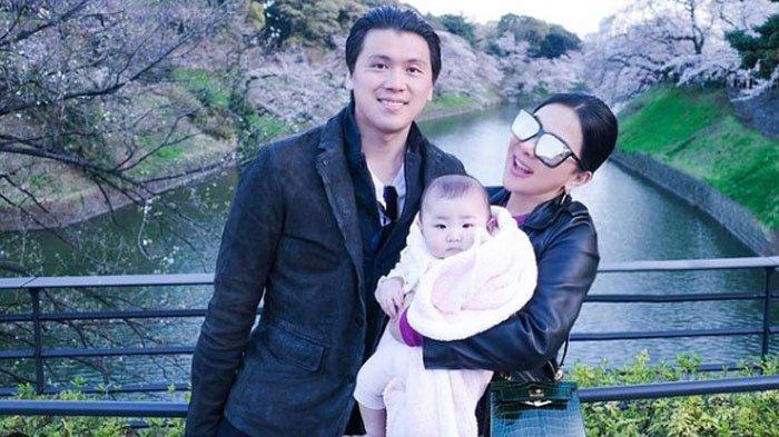 Syahrini pamer foto romantis bersama Reino Barack. ia juga tampak menggendong seorang bayi dalam foto tersebut.