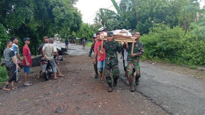 TNI dan warga menggotong seorang warga yang jadi korban banjir di wilayah Ile Ape, Kabupaten Lembata, Minggu 4 April 2021.