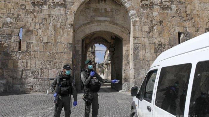 Polisi perbatasan Israel mengenakan topeng pelindung di tengah patroli wabah COVID-19 di sekitar Gerbang Singa di Kota Tua Yerusalem, Rabu (25/3/2020).