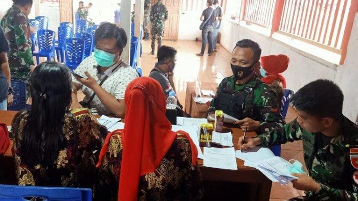 TNI-AD terlihat melayani seorang warga yang ingin mengikuti vaksinasi massal di Desa Sari Mukti, Kecamatan Langkikima, Konawe Utara, Sulawesi Tenggara, Jumat (20/8/2021).