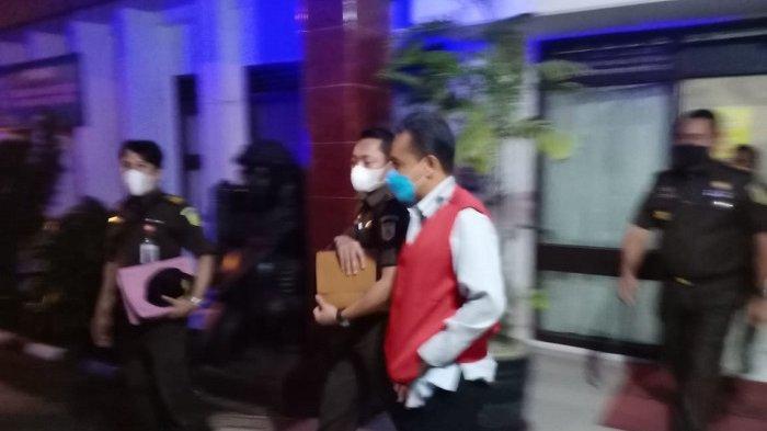 Buhardiman keluar dari ruang penyidik Kejaksaan Tinggi atau Kejati Sultra dengan menggunakan rompi merah tahanan.