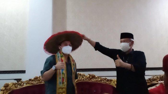 Wakil Gubernur Sulawesi Tenggara atau Wagub Sultra Lukman Abunawas memberikan penutup kepala dan mengalungkan syal tenun Tolaki ke Apriyani Rahayu, Sabtu (28/8/2021).