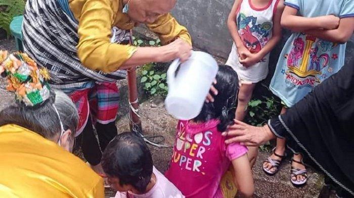 Seorang tetua adat di Kelurahan Kadolomoko, Kota Baubau, Sulawesi Tenggara, tengah memandikan anak yatimpiatu, Kamis (19/8/2021). Ritual memulai Pekansena Anaana Maelu.