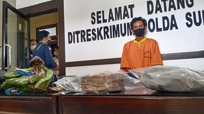 Tersangka praktek penggandaan uang palsu S (50) beserta barang bukti uang palsu, pisang, kain kafan.(Foto: Fadli Aksar)