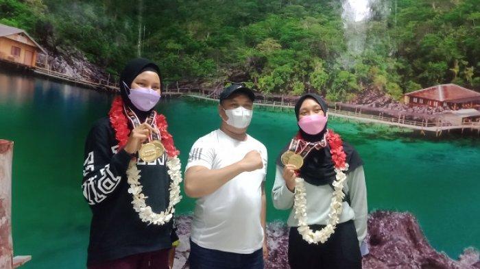 Dua atlet dayung peraih medali emas PON XX Papua, Aulia Ghaib dan Julianti foto bersama Bupati Konawe Utara, saat tiba di Bandara Halu Oleo Kendari.