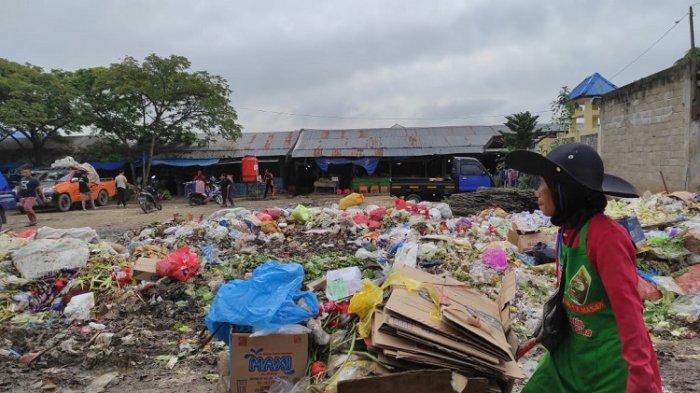 SAMPAH- Petugas kebersihan saat mengangkut sampah yang menumpuk di Tempat Pembuangan Sampah (TPS)