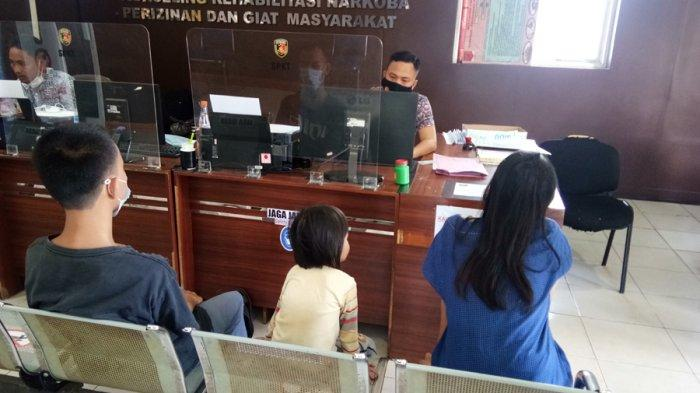 PAHMI/TRIBUNSUMSEL Nel sebalah kanan dan anaknya SA membuat laporan di SPKT Polrestabes Palembang, Selasa (9/3/2021).