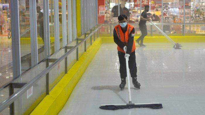 Riando, Seorang rink guard mengepel arena ice skating untuk kenyamanan dan keamanan saat bermain.