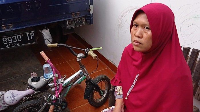 Mardiana (38) ibu kandung Dzaky Ichsandra, bocah 4 tahun yang diduga jadi korban penculikan, duduk disebelah sepeda yang sempat dimainkan anaknya sebelum akhirnya jadi korban diduga penculikan, Jumat (19/2/2021) siang.