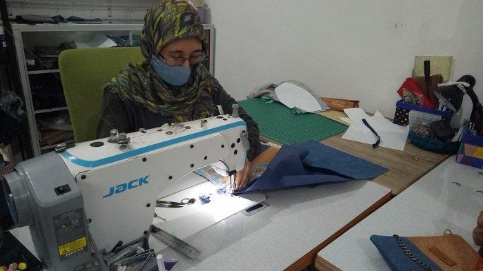 Masayu Maryani menjahit tas dengan seni Patchwork yang berasal dari Amerika di rumahnya yang beralamat di Jalan Sulaiman Amin, Palembang